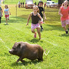 Children chase after a pig during the Piglet Chase event at the Fete for Pets fundraiser Saturday, March 31, 2012. (Les Hassell/News-Journal Photo)
