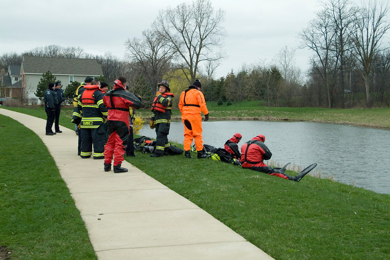 Divers getting ready to go into the pond to hook a Mercedes Benz that ended up in there the night before.