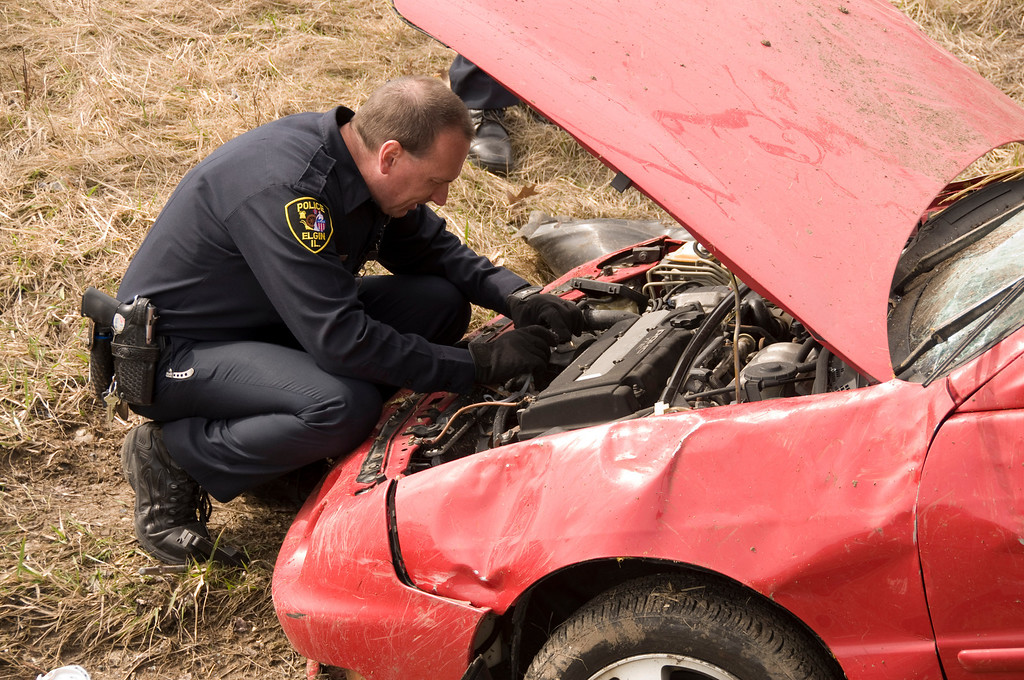 EPD officer Zac McCorkle takes pictures of the engine compartment and serial number of the engine.