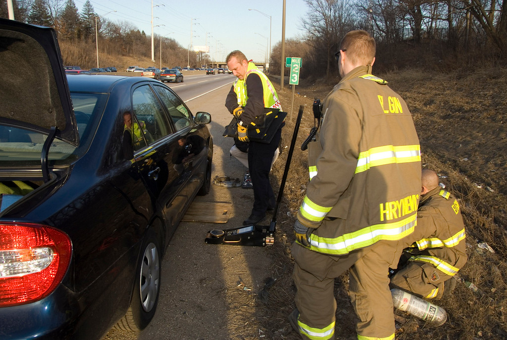 Elgin Firefighters helping someone change a tire on the tollway after his car fell off the jack.