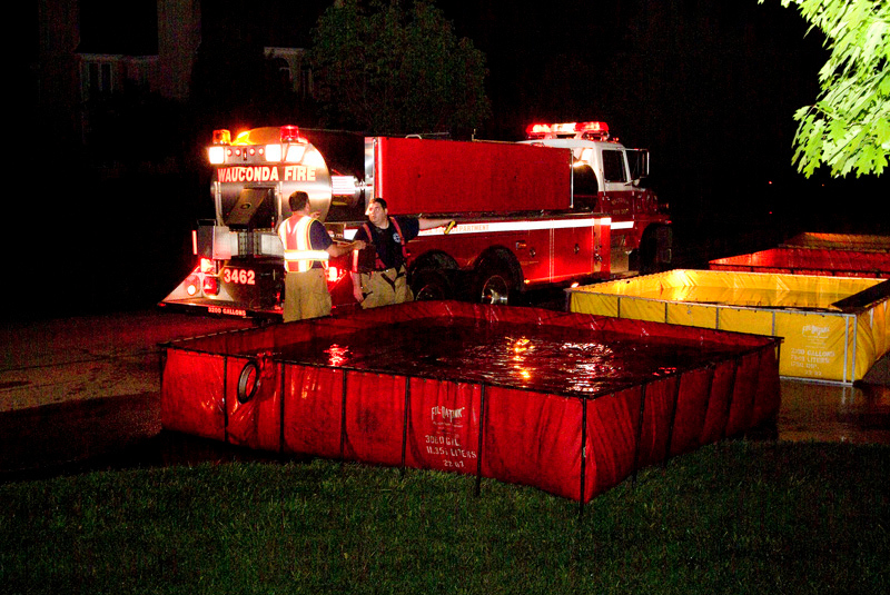 A Wauconda tender fills one of the 4 portable tanks (holding 11,000 gallons) set up in the streets near the house.  <br /> <br /> 10,000 gallons were used to extinguish the blaze.