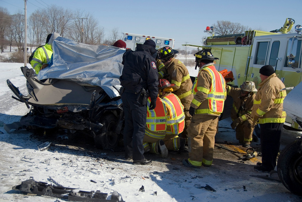 Firefighters and Police doing their best to keep the 20mph+ wind from blowing on the driver of the vehicle.  The wind-chill during this extrication was -25°!