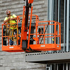 A worker clontinues construction of the new Windsor Foods plant on East 32nd street on Wednesday.<br /> Globe | Laurie Sisk