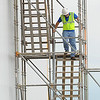 A worker climbs down scaffolding at the construction site of the new Windsor Foods plant on East 32nd street on Wednesday. <br /> Globe | Laurie Sisk