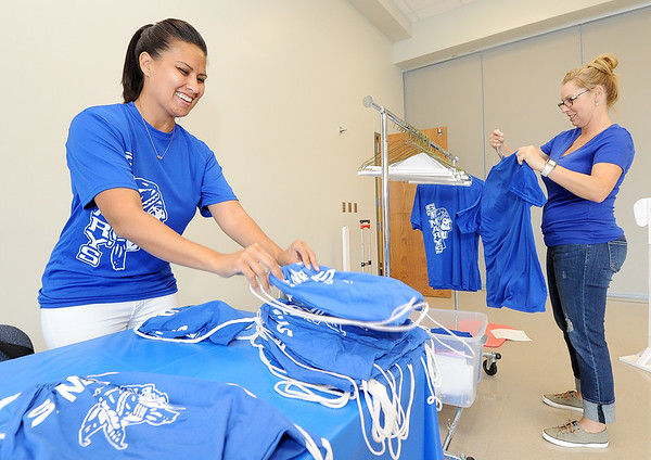 From the left: Sally Robinson and Tami Veer, of St. Mary's Elementary Home and School, organize cinch sacks and spirit shirts prior to Open House on Sunday at St. Mary's Elementary. Home and School - a parent/teacher organization - created the cinch sacks from previous year's t-shirts.<br /> Globe | Laurie Sisk