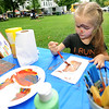 "Budding artist Riley Thurlow, 4, paints a wall switch plate and her face at the Carthage Water and Electric Plant's ""Come paint"" booth in Central Park on Friday during Carthage's Food Truck Friday.<br /> Globe 