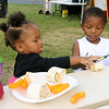 from the left: Jaedah Dawson, 1, shares part of her plate with Jayceon Caldwell, 2, on Saturday during the annual Emancipation Park Days at Ewert Park.<br /> Globe | Laurie Sisk