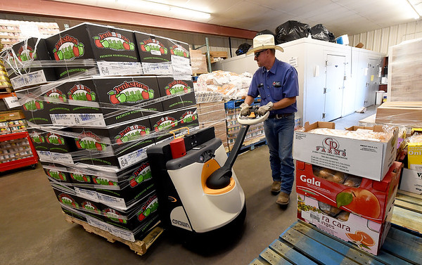 Ozarks Food Harvest driver Chad Baker unloads a pallet of apples from a 30,000 pound food delivery to Crossslines last month.<br /> Globe | Laurie Sisk