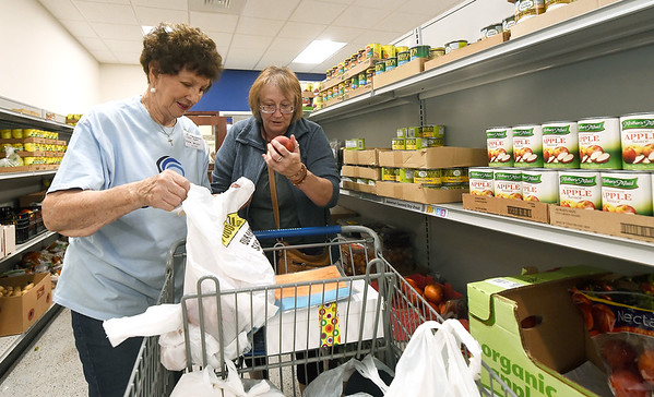 From the left: Crosslines volunteer Dixie Springer, from First Christian Church, assists Tammy McGuirk with her groceries on Thursday at Crosslines. Globe | Laurie Sisk