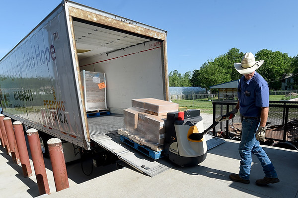 Ozarks Food Harvest driver Chad Baker, unloads a truck containing about 30,000 pounds of food last month at Crosslines. Globe | Laurie Sisk