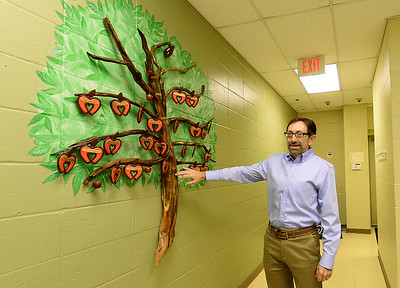 Ozarks Food Harvest CEO Bart Brown stands beside the Charles Foltz Gift of Time Tree that honors long serving volunteers. Volunteers are moved up the tree as they serve more hours. The tree is named in honor of longtime volunteer Charles Foltz. Globe | Laurie SIsk