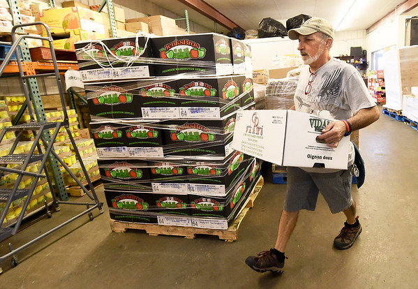 Crosslines warehouse manager Dan Ashton helps organize produce from a 30,000 pound Ozark Food Harvest food delivery last month at Crosslines. Globe | Laurie Sisk