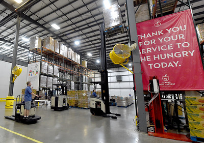 Workers at Ozarks Food Harvest in Springfield rotate inventory in one of two large warehouses last month. Globe | Laurie Sisk