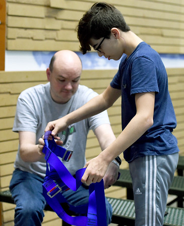 Mike Brown helps Braiden Windle, 14, with his harness for a climbing wall at Victory Ministry and Sports Complex on Saturday.<br /> Globe   Laurie Sisk