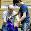 Mike Brown helps Braiden Windle, 14, with his harness for a climbing wall at Victory Ministry and Sports Complex on Saturday.<br /> Globe | Laurie Sisk