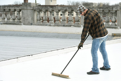 Brandon Calliote sweeps construction debris from the Gadarian Event Center's rooftop venue that is currently under construction on the Carthage square. Globe   Laurie SIsk