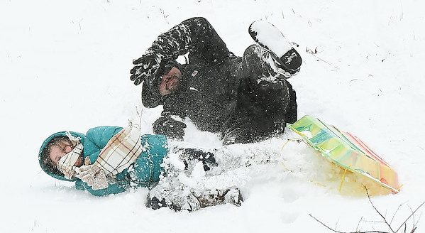 Seven-year-old Bree Pilcher and her dad, Garrett Pilcher enjoy a slide down a hill at Landreth Park on Wednesday after heavy snow hit the area overnight and well into the day.<br /> Globe | Laurie Sisk