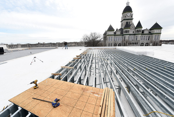 Brandon Calliote sweeps construction debris from the Gadarian Event Center's rooftop venue that is currently under construction on the Carthage square.<br /> Globe | Laurie SIsk