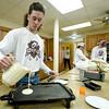 Joplin High School senior Mitchell Eldridge pours more batter for pancakes during a benefit pancake feed for the Joplin High School Bass Fishing Club on Saturday at South Joplin Christian Church.<br /> Globe | Laurie Sisk
