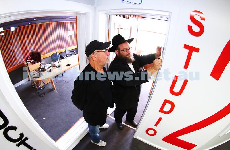 18-2-15. David Edelman looks on as Eli Gutnick ataches mezuzahs to the doors of the new J - Air studios in Chadstone. Photo: Peter Haskin