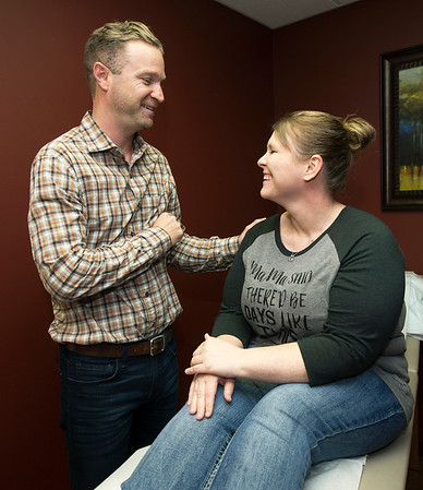 Dr. David Baker, general surgeon at the Freeman Bariatric Center, chats with post-surgery patient and co-worker, Rebecca Wilkinson on Wednesday at the center. Wilkinson, a CMA at the center, has lost 85 lbs. since her bariatric surgery.<br /> Globe | Laurie Sisk