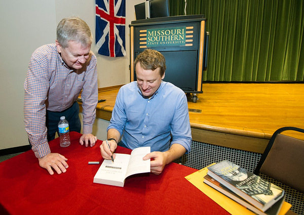 "Author Charles Finch, right,  signs a copy of his novel, ""The Last Enchantments,"" for Missouri Southern Director of International Studies Chad Stebbins on Wednesday at MSSU's Corley Auditorium. The event was held in conjunction with MSSU's Great Britain semester.<br /> Globe 