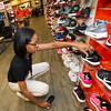 Hibbett Sports sales associate Cherita Ingram organizes children's shoes on a display wall in preparation for Black Friday on Tuesday at the Northpark Mall store.<br /> Globe | Laurie Sisk