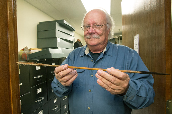 Steve Weldon, director of the Jasper County Records Center, holds an arrow that was pulled from a man's skull. The arrow, along with many stacks of historic artifacts and documents, are housed at the center.<br /> Globe | Laurie Sisk