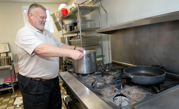 Carthage Crisis Center Executive Director Jim E. Benton helps prepare the Friday evening meal in the same kitchen that will soon begin preparing for about 450 meals for those in need.<br /> Globe | Laurie Sisk