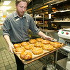 Panera Bread Company manager Max Barnett transports a tray of bagels on Thursday at the Joplin store. His crew has repeated as national champions in the company's Pink Ribbon Bagel campaign, besting second place Fort Smith, Ark. for the title.<br /> Globe | Laurie Sisk