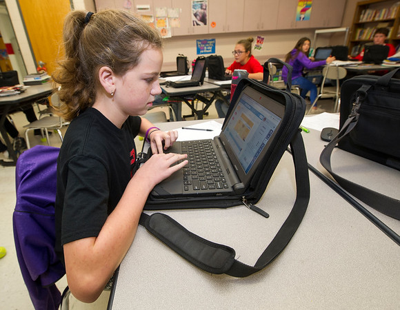 Carl Junction sixth grader Melia Chase uses her district-supplied laptop to research famous scientists on Friday in Christine Lange's sixth grade science class on Friday at Carl Junction Intermediate.<br /> Globe | Laurie Sisk