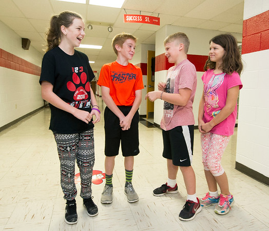 """From the left: Carl Junction sixth graders Melia Chase, Zachary Merwin, Keaton Amos and JAnie McCleary chat under a """"Success"""" street sign in a hallway on Friday at Carl Junction Intermediate School. <br /> Globe 