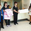 From the left: Mercy volunteer and quilt artist Marie Judd, quilt winner Susan Jones, Lisa Nelson, of Sisters Health Boutique and Miranda Lewis, executive director of the Mercy Health Foundation, pose with a mock check for $655 from the proceeds of a quilt raffle on Wednesday morning at Mercy Hospital Joplin. Salon 529 also donated $450 - the proceeds from pink nails and hair extensions.<br /> Globe | Laurie Sisk