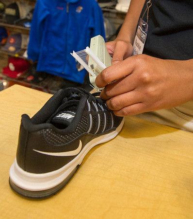 Hibbett Sports sales associate Cherita Ingram tags children's shoes in preparation for Black Friday on Tuesday at the Northpark Mall store.<br /> Globe | Laurie Sisk