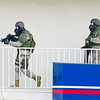 Joplin Police SWAT officers, armed with a K-9 officer, prepare to breach the door where they believe a suspect, Don Loomis is hiding at the Motel 6 on Rangeline on Wednesday. The stand-off began about 9 a.m. and continued well into the afternoon hours.<br /> Globe | Laurie Sisk
