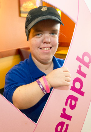 Panera Bread Company Associate Trainer Dani O'Dell shows off the pink ribbon bracelet she wears on a daily basis on Thursday at the Joplin store. O'Dell is part of a crew that has repeated as national champions in the company's Pink Ribbon Bagel campaign.<br /> Globe | Laurie Sisk