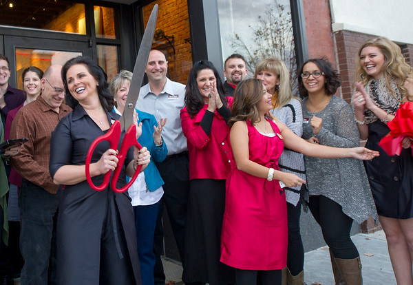 Flanked by staff and members of the Joplin Area Chamber of Commerce, Rapha House founder Stephanie Freed, left, celebrates the opening of the Rapha House Gallery and Freedom Boutique on Friday. The boutique features items made by girls rescued from exploitation or slavery. All proceeds from the sale of items at the boutique advance the fight and help young girls recover from their exploitation.<br /> Globe | Laurie SIsk