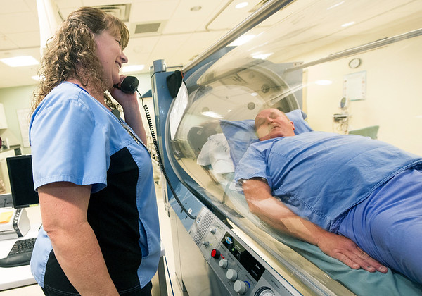 Mercy Clinical Nurse Coordinator Chris Bulita, left, uses a phone to communicate with diabetes patient Jim Cummings during a demonstration of a hyperbaric treatment on Tuesday at the Mercy Wound Care and Hyperbaric Medicine. Cummings recently received hyperbaric treatment s to heal a diabetes-related wound on his foot.<br /> Globe   Laurie Sisk