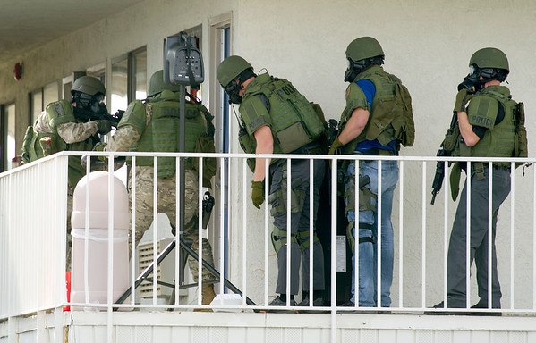 Joplin Police SWAT officers breach the door where they believe a suspect, Don Loomis is hiding at the Motel 6 on Rangeline on Wednesday. The stand-off began about 9 a.m. and continued well into the afternoon hours.<br /> Globe | Laurie Sisk