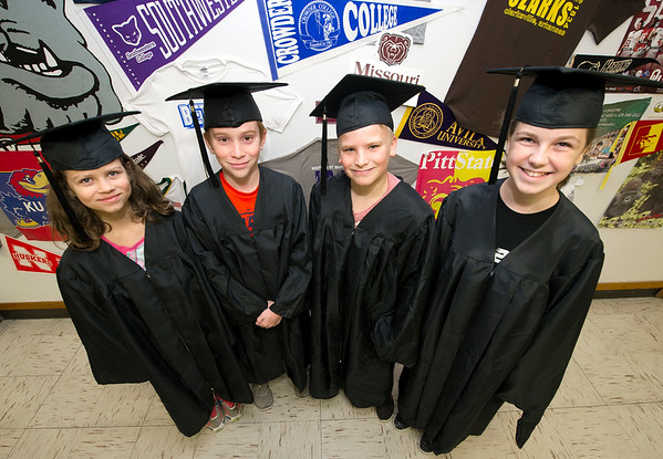 "From the left: Carl Junction sixth graders Janie McCleary, Zachary Merwin, Keaton Amos and Melia Chase keep their eyes on the prize as they don their ""halfway there"" caps and gowns on Friday at Carl Junction Intermediate School. All sixth graders will have their pictures taken in caps and gowns by semester's end as a reminder that they are at the halfway point to becoming high school graduates.<br /> Globe 
