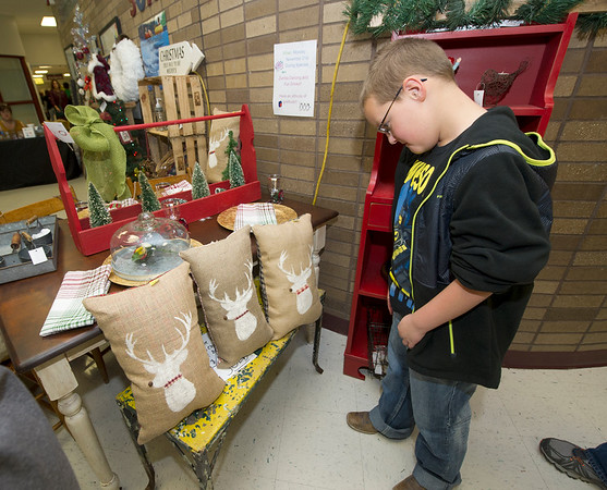 Eight-year-old Austin Hirsch, of Mount Vernon, checks out reindeer piilows at the Cecil Floyd Elementary School Craft Fair on Saturday at the school.<br /> Globe | Laurie Sisk
