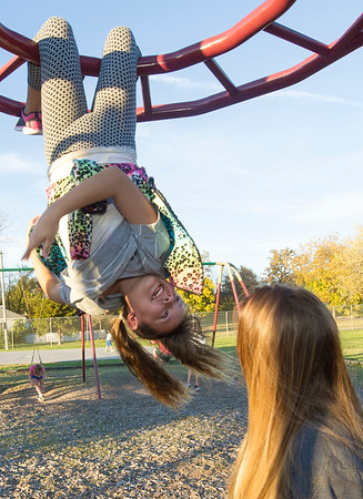 Ten-year-old Sitara Raymond hangs from the monkey bars as she chats with Joplin High School Interact volunteer Natalie Goodhue last week at the Boys and Girls Club of Southwest Missouri.<br /> Globe | Laurie Sisk