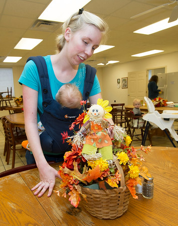 Brooke Fry, operations assistant at the Carthage Crisis Center, straightens a Thanksgiving-themed table arrangement on Friday at the Carthage Crisis Center. Also pictured is three-month-old Orson Fry.<br /> Globe | Laurie Sisk