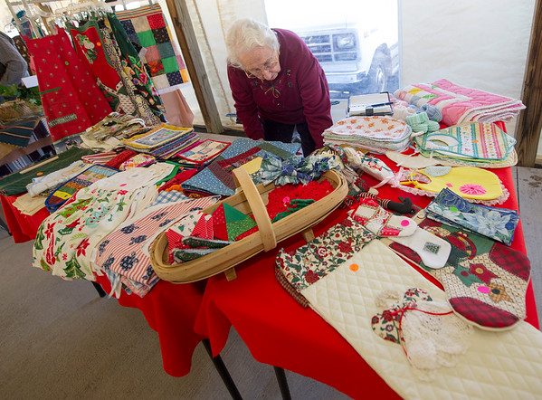 "Edith Bayless arranges her "" Edith's Sewn Goods"" booth full of handmade items on Saturday at the Christkindlmarket inside the Webb City Farmer's Market.<br /> Globe 