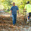 "From the left: Braden Horst, president of the Joplin Trails Coalition, walks the Ruby Jack Trail in Carthage with his labrador, ""Ike"" as boardmember Robert Blackford rides past on Thursday.<br /> Globe 