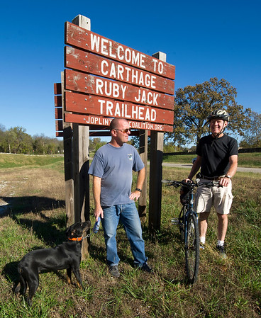"From the left: Braden Horst, president of the Joplin Trails Coalition, stands at the entrance of the Ruby Jack Trail with his labrador, ""Ike"" and boardmember Robert Blackford on Thursday.<br /> Globe 