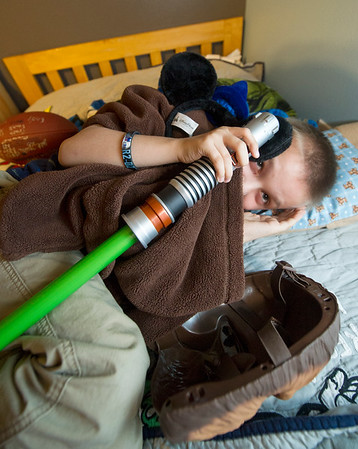 Playing a little camera shy, seven-year-old Peyton Vanderpool cuddles up with his Chewbacca outfit on Wednesday at his Carl Junction home.<br /> Globe | Laurie Sisk