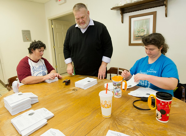 Carthage Crisis Center Executive Director Jim Benton, center, helps residents Denna Henslee, left and her daughter, Mindy Henslee prepare the center's monthly newsletter for delivery to more than 140 area churches and organizations on Tuesday at the center.<br /> Globe | Laurie Sisk