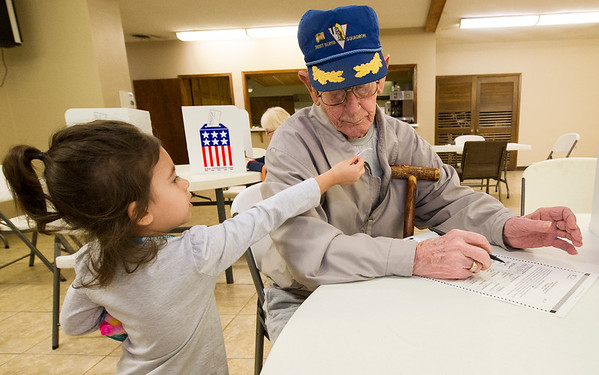 "Three-year-old Violet Marquez hands her great-great-grandfather, WWI Veteran Harvey Erwin, 94, an ""I Voted"" sticker as he studies his ballot on Tuesday at the Church of Brookwood. Erwin flew 25 missions as a tail gunner with the 781st Bomb Squadron in World War II.<br /> Globe 