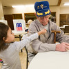 """Three-year-old Violet Marquez hands her great-great-grandfather, WWI Veteran Harvey Erwin, 94, an """"I Voted"""" sticker as he studies his ballot on Tuesday at the Church of Brookwood. Erwin flew 25 missions as a tail gunner with the 781st Bomb Squadron in World War II.<br /> Globe 